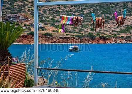 Traditional Sun-dried Octopuses Clipped To Rope With Typical Greek Hills And Fishermens Boat In Back