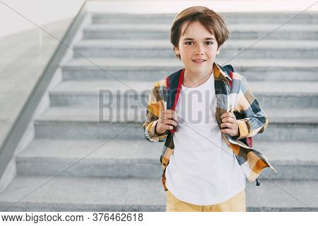 A Happy Boy With A Backpack Stands On The Steps In Front Of The Entrance To The School And Smiles Be