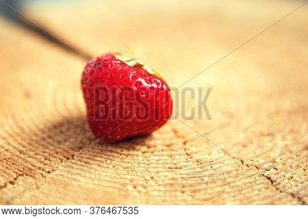 One Red Strawberry On The Wooden Background, Close Up
