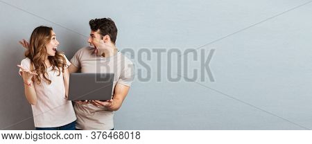 Portrait of a cheery happy couple holding laptop computer while standing and celebrating isolated over gray wall background