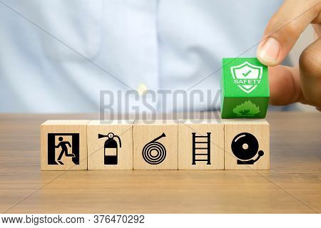 Close-up Hand Choose Prevent Symbol On Cube Wooden Toy Blocks Stacked With Fire Exit Icon For Fire S
