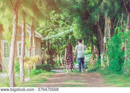 Couple Walking And Taking Photos Under The Pine Trees In The Public Park.