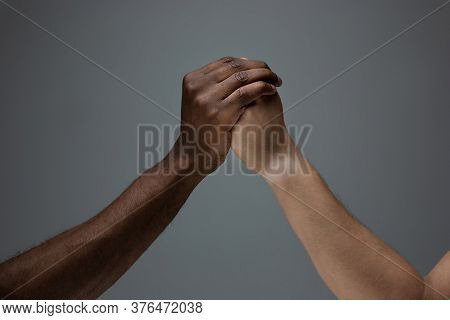 Togetherness. Racial Tolerance. Respect Social Unity. African And Caucasian Hands Gesturing On Gray