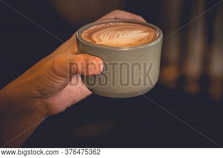 Hand Holding A Cup Of Latte Coffee Top View Showing Latte Art In Leaf Shape