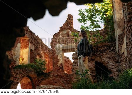 Young Tourist Woman Stands By Archway Of Old Ruined Castle Building, Halshany, Belarus