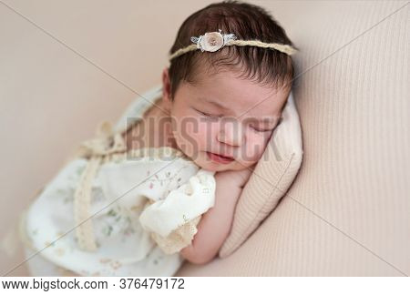 Nice newborn hugging toy sleeping on side on tiny pillow