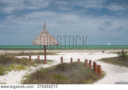 Deserted Tropical Beach With Natural Umbrella. Palm Leaf Umbrella. In The Background A Sailing Ship