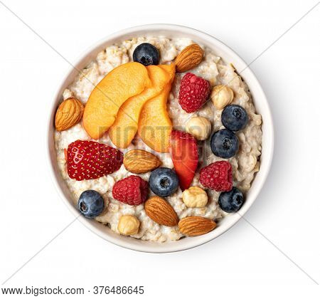 prepared oatmeal with fruits and berries isolated on white background