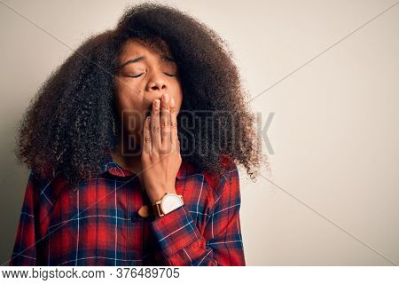 Young beautiful african american woman wearing casual shirt over isolated background bored yawning tired covering mouth with hand. Restless and sleepiness.
