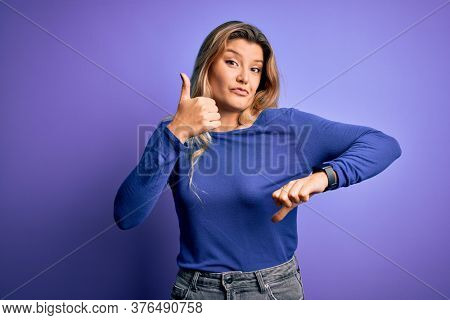 Young beautiful blonde woman wearing casual t-shirt over isolated purple background Doing thumbs up and down, disagreement and agreement expression. Crazy conflict