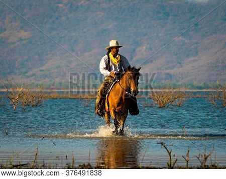 A Western Cowboy Was Riding A Horse To Wade Through The Lake Area, With The Background In The Mounta