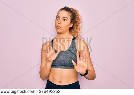 Young beautiful blonde sportswoman with blue eyes doing exercise wearing sportswear Moving away hands palms showing refusal and denial with afraid and disgusting expression. Stop and forbidden.