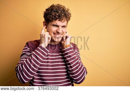 Young blond handsome man with curly hair wearing casual striped sweater covering ears with fingers with annoyed expression for the noise of loud music. Deaf concept.