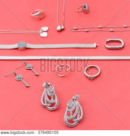 Silver Jewelry On Minimal Pink Background. Rings, Bracelets And Earrings. Top View Of Fashion Woman