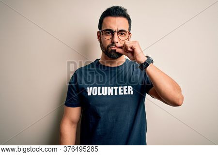 Handsome man with beard wearing t-shirt with volunteer message over white background mouth and lips shut as zip with fingers. Secret and silent, taboo talking