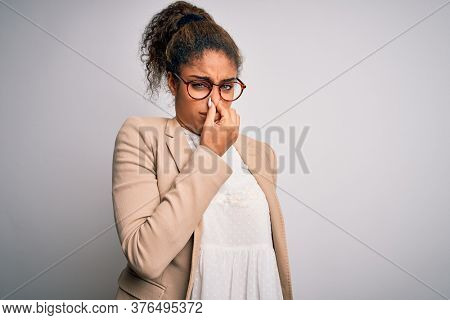 Beautiful african american businesswoman wearing jacket and glasses over white background smelling something stinky and disgusting, intolerable smell, holding breath with fingers on nose. Bad smell