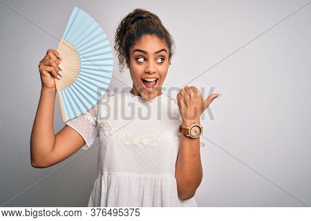 Young african american girl using hand fan to refreshment over isolated white background pointing and showing with thumb up to the side with happy face smiling