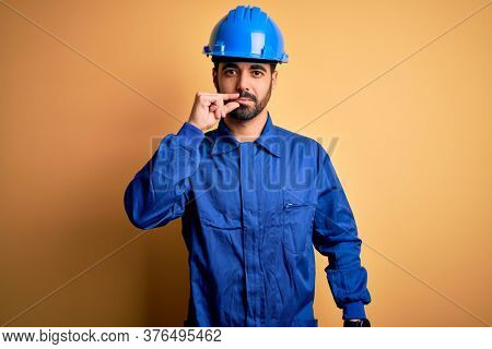 Mechanic man with beard wearing blue uniform and safety helmet over yellow background mouth and lips shut as zip with fingers. Secret and silent, taboo talking