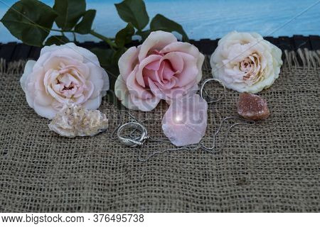 On Jute Fabric Are Semiprecious Stones Rose Quartz, Dolomite, Halite. Nearby Are Silver Rings And A