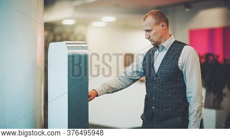 A Serious Caucasian Businessman In A Plaid Vest Is Using An Indoor Office Electronic Terminal To Mak