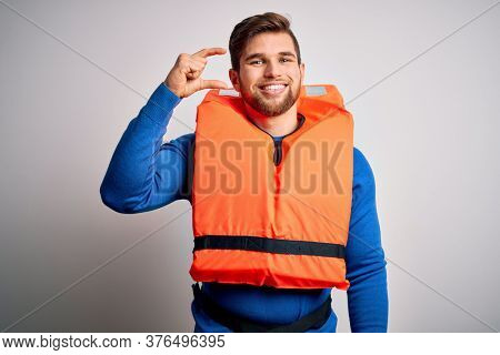 Young blond tourist man with beard and blue eyes wearing lifejacket over white background smiling and confident gesturing with hand doing small size sign with fingers looking and the camera. Measure.