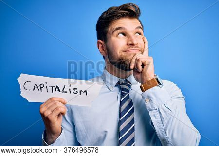 Young blond businessman with beard and blue eyes holding paper with capitalism message serious face thinking about question, very confused idea