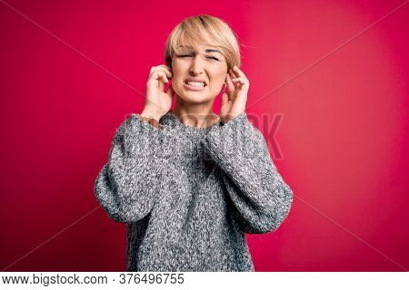 Young blonde woman with modern short hair wearing casual sweater over pink background covering ears with fingers with annoyed expression for the noise of loud music. Deaf concept.