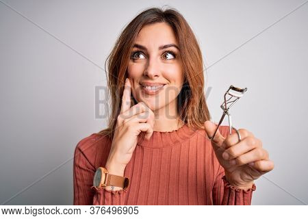 Young beautiful brunette woman using eyelash curler over isolated white background serious face thinking about question, very confused idea