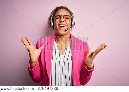 Young african american call center agent girl wearing glasses working using headset celebrating mad and crazy for success with arms raised and closed eyes screaming excited. Winner concept