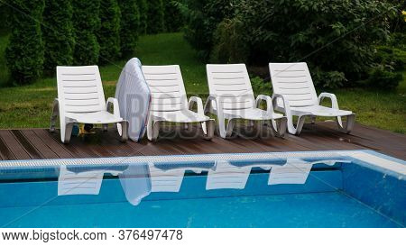 Top View Of Chairs Of A Swimming Pool With Blue Water Outside In The Garden