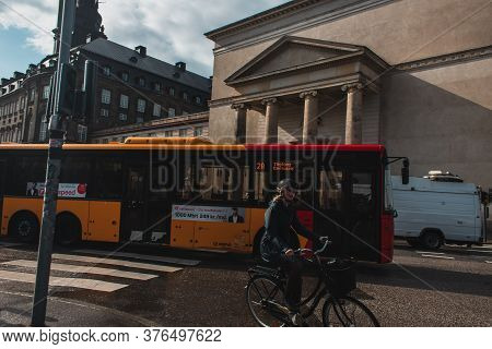 Copenhagen, Denmark - April 30, 2020: Woman Riding Bicycle Near Buses On Urban Street