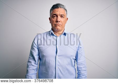Middle age handsome grey-haired business man wearing elegant shirt over white background depressed and worry for distress, crying angry and afraid. Sad expression.