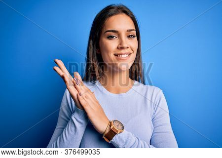 Young beautiful brunette woman wearing casual sweater standing over blue background clapping and applauding happy and joyful, smiling proud hands together
