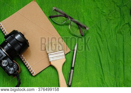 A Notebook, A Photo Camera, Glases, Brush And Pen