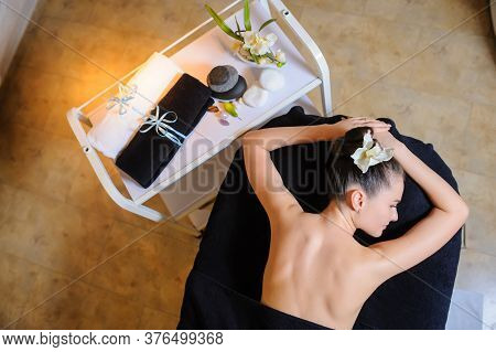 Women Laying Down On The Massage Bed In The Spa With A Flower