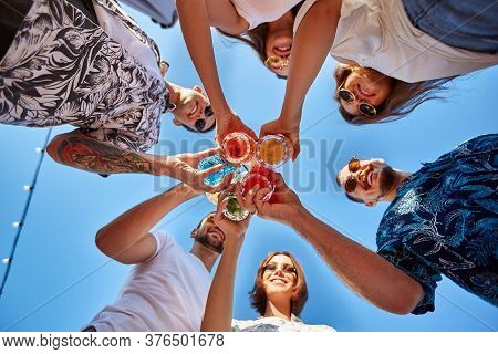 Low Angle View Of Friends Having Fun At Poolside Summer Party, Clinking Glasses With Colorful Summer