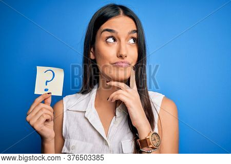 Young beautiful brunette woman holding paper with question mark symbol message serious face thinking about question, very confused idea
