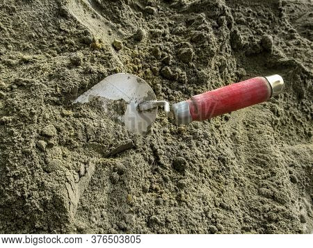 Metal Trowel With A Red Wooden Handle On A Background Of Gray-brown Dry Sand-cement Mortar. Construc