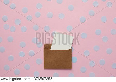White Blank Card In Kraft Brown Paper Envelope On Pink Background With Confetti. Holiday Mockup. Top