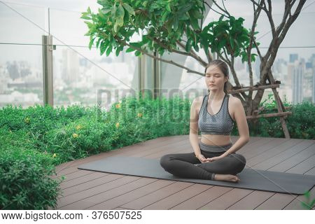 Young Asian Woman Practicing Meditation On The Rooftop .