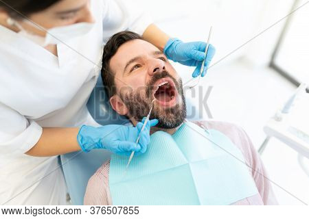 Female Doctor Examining Mid Adult Man With Dental Mirror And Carver At Clinic