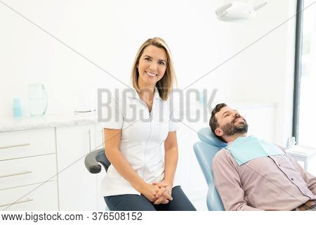 Confident Caucasian Female Dentist With Mid Adult Man At Clinic