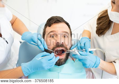 Portrait Of Mid Adult Man Keeping Mouth Open And Looking Scared While Dentists Examine Teeth With To