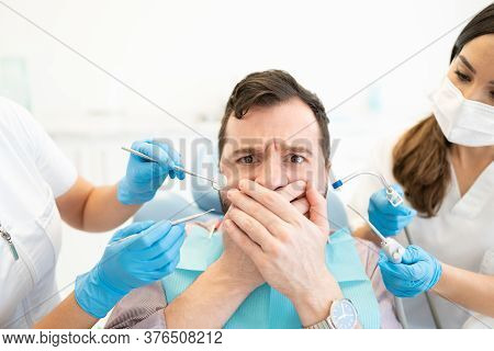 Frightened Mid Adult Man Covering Mouth While Dentist Holding Tools During Treatment