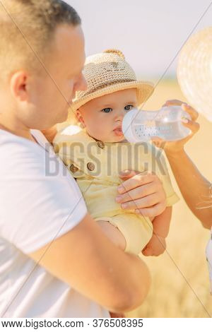 Young Parents Feed Their Baby By Milk From Feeding-bottle While Outing.