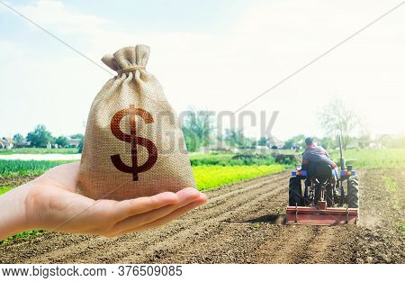 A Hand Holds Out A Dollar Money Bag On A Background Of A Field Cultivating Tractor. Lending Farmers