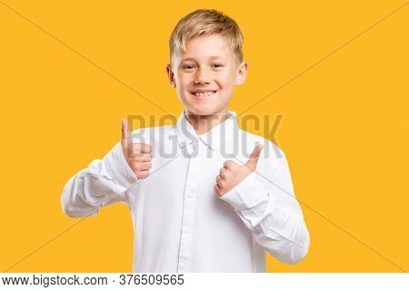 Like Gesture. Approval Sign. Cheerful Boy In White Shirt Showing Thumbs Up Isolated On Orange Backgr