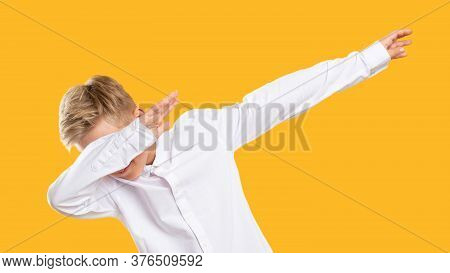 Dab Gesture. Dance Move. Amused Boy Raising Arms Dropping Head In Confident Posture Isolated On Oran
