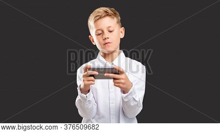 Mobile Game Addiction. Online Entertainment. Confident Boy Playing On Smartphone Isolated On Dark Ba