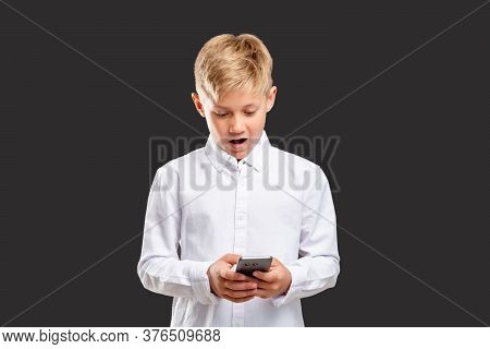 Online Communication. Impressive News. Surprised Boy Reading Message On Phone Isolated On Dark Backg